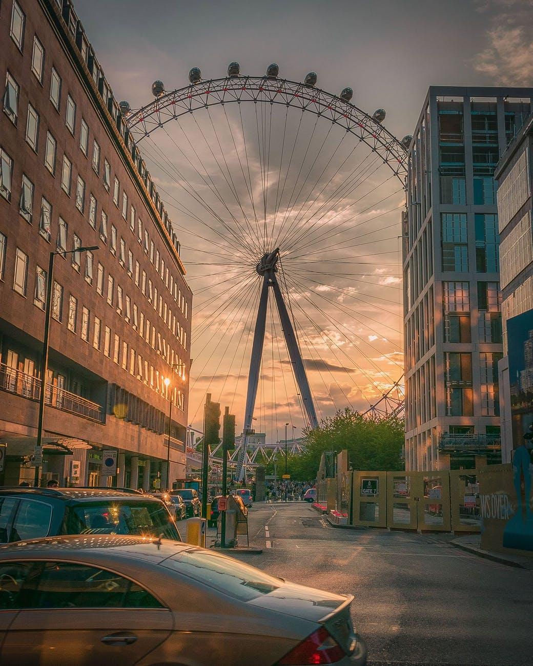 ferris wheel near building during sunset